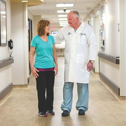 Orthopedic surgeon walking with patient