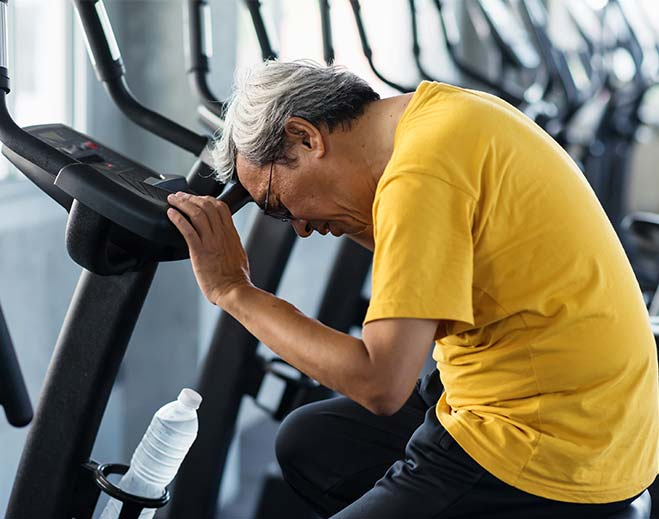 elderly man dizzy on exercise bike